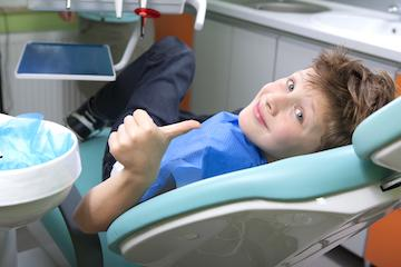 Young boy laying in dental exam chair smiling at Family dentist in Aston PA