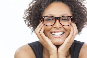 Woman smiling holding face in her hands wearing Invisalign in Aston PA