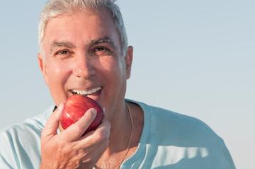 Man eating an apple with dentures in Aston, PA